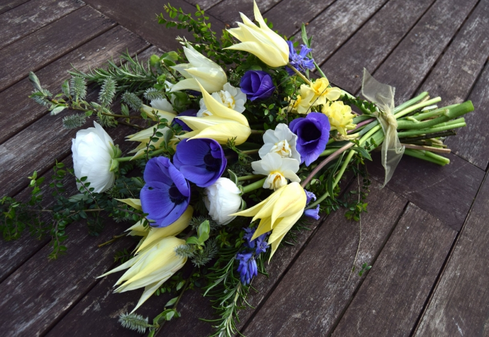 Natural Spring funeral spray in blue and yellow